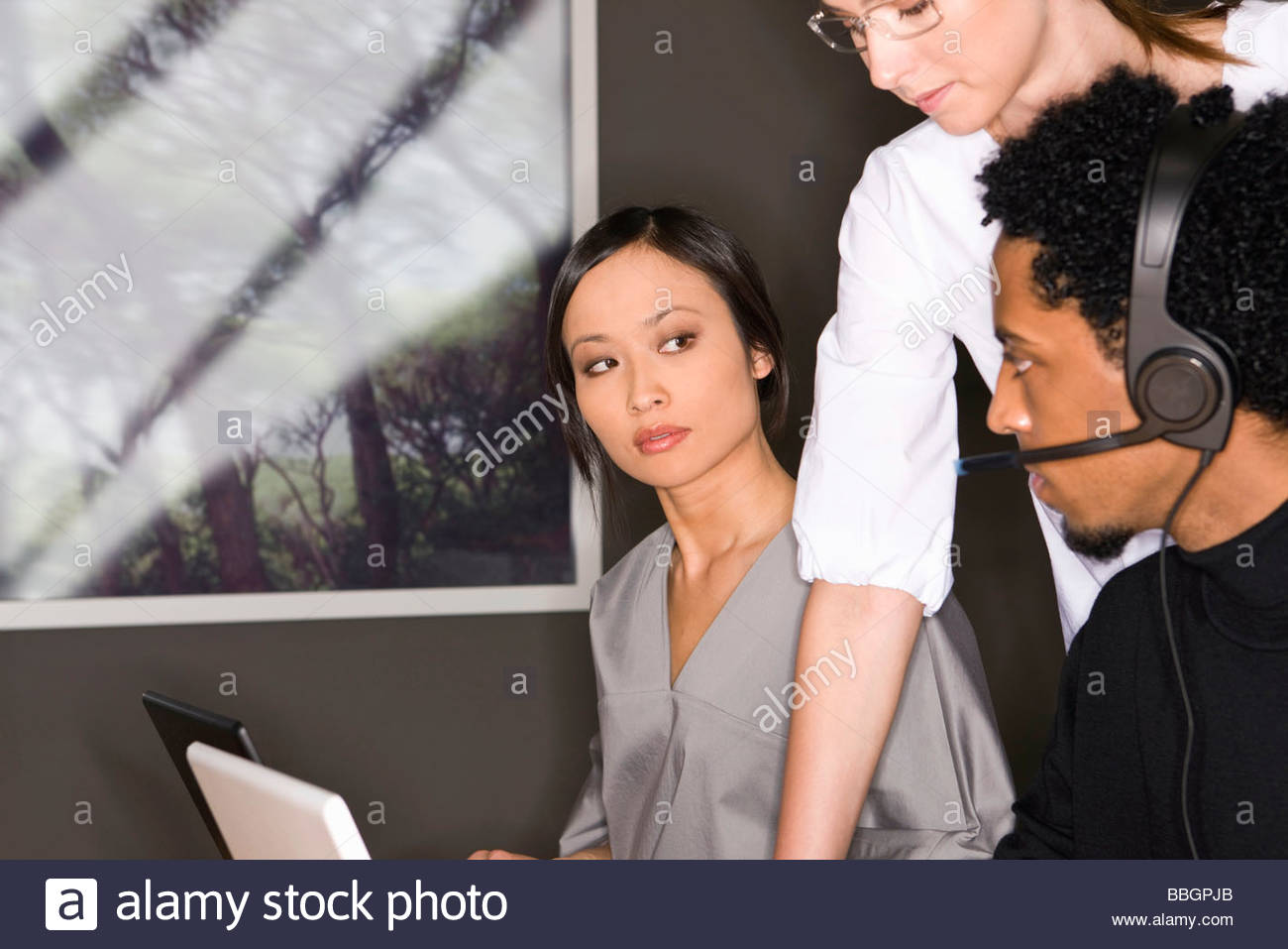 Young Asian businesswoman looking at African man office Stock Photo
