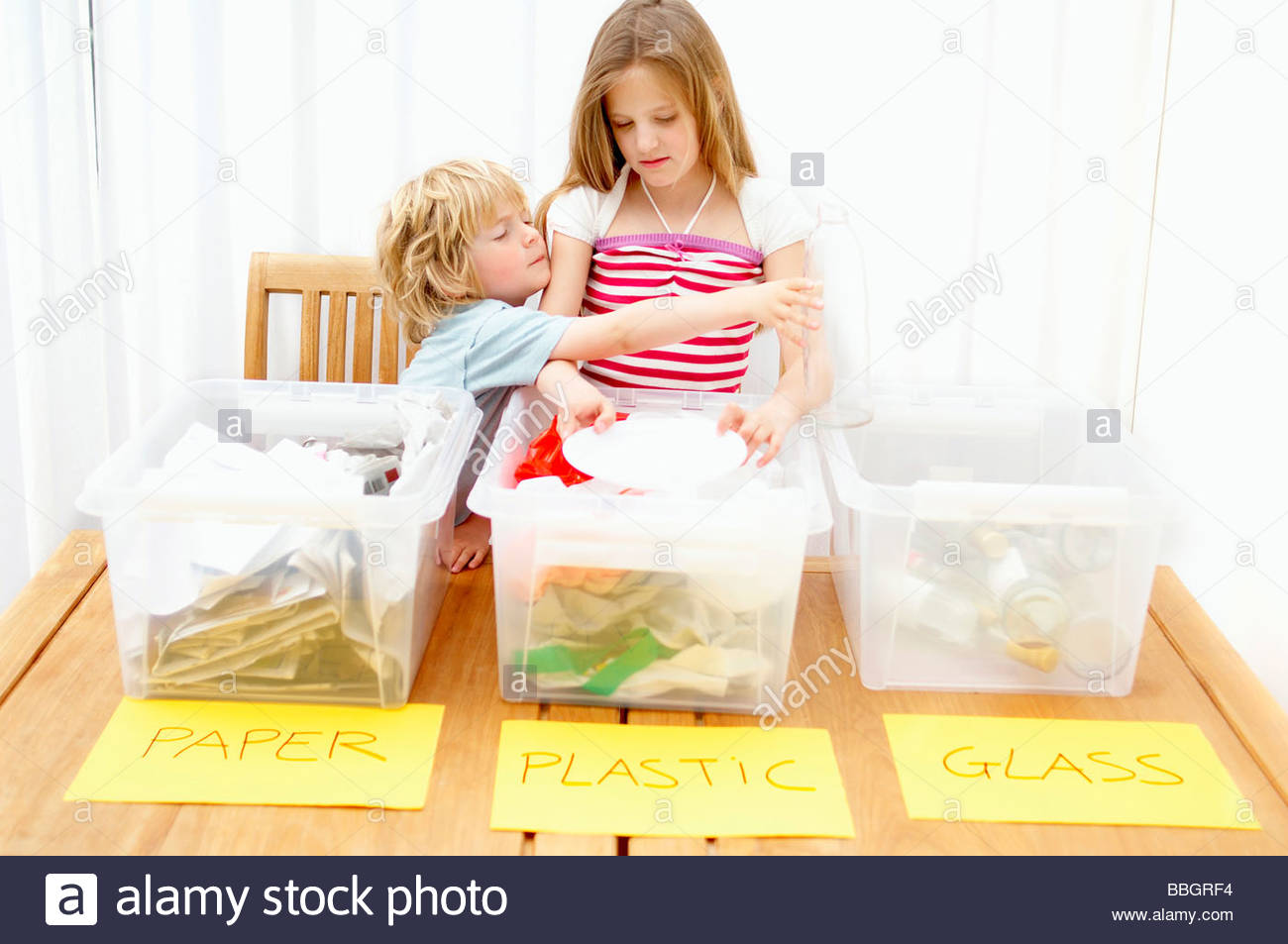 Boy and girl separating paper, plastic and glass, Den Haag, Netherlands - Stock Image