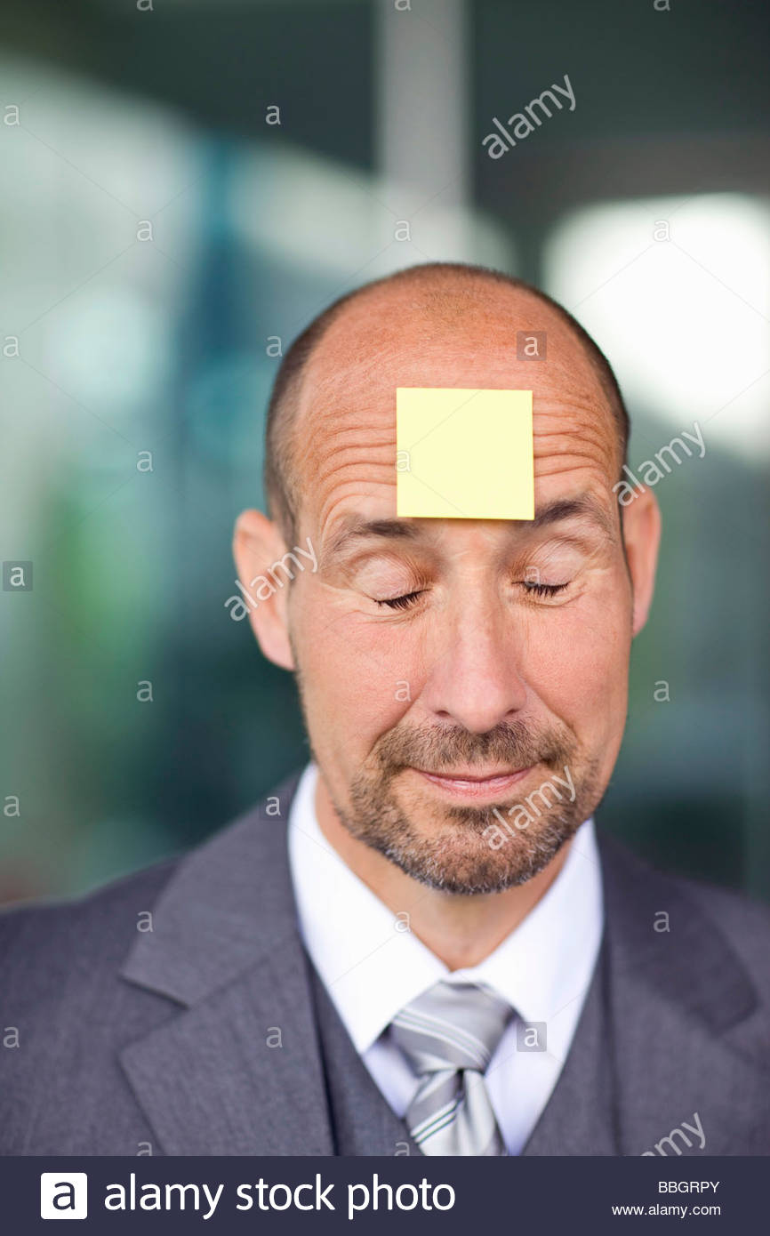 Portrait mature man with note paper stuck on forehead - Stock Image