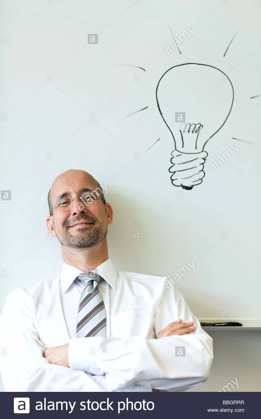 Portrait mature man sitting beneath a line drawing light bulb - Stock Image