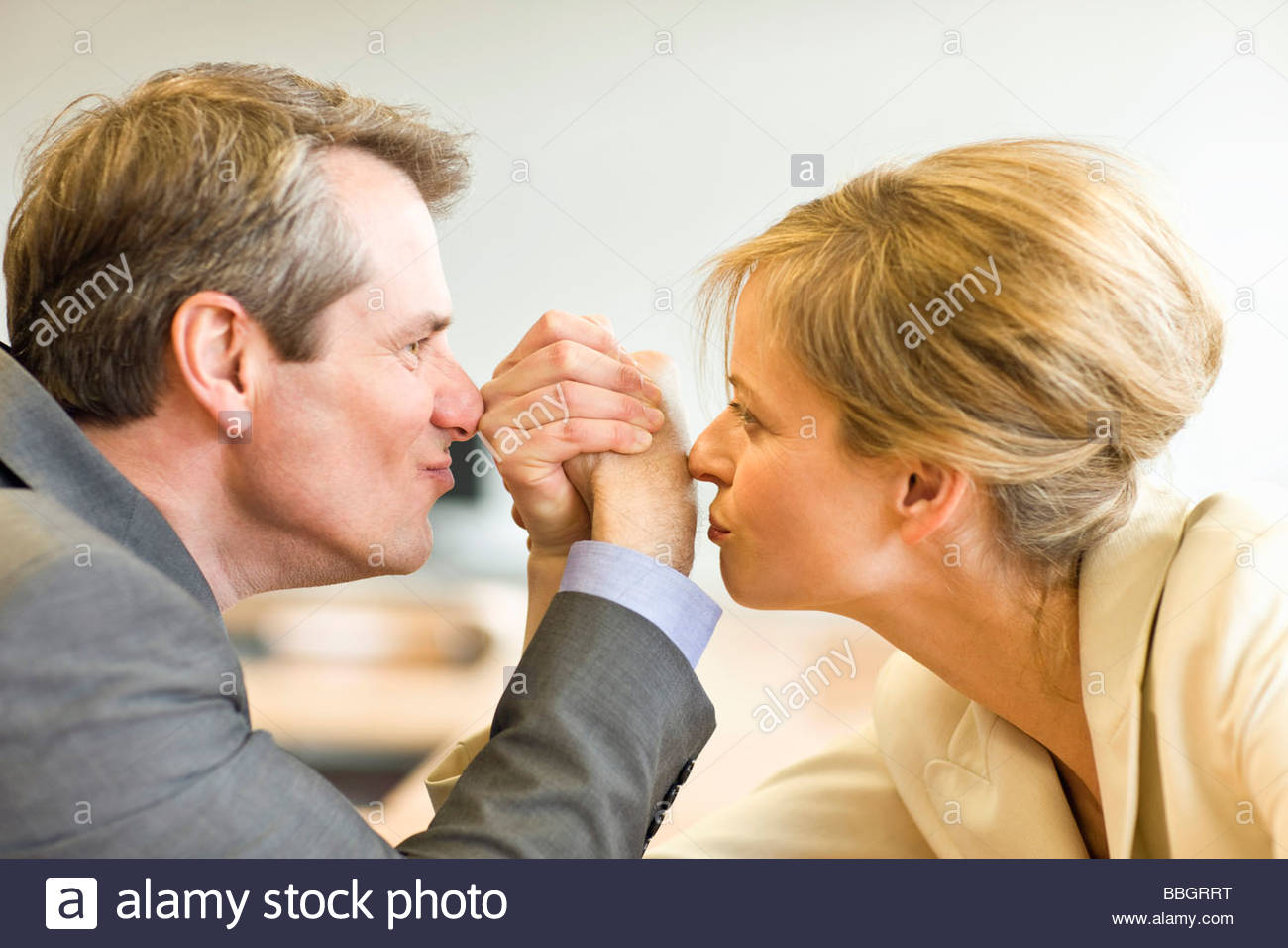 Mature man and woman enjoying a friendly bout arm wrestling - Stock Image