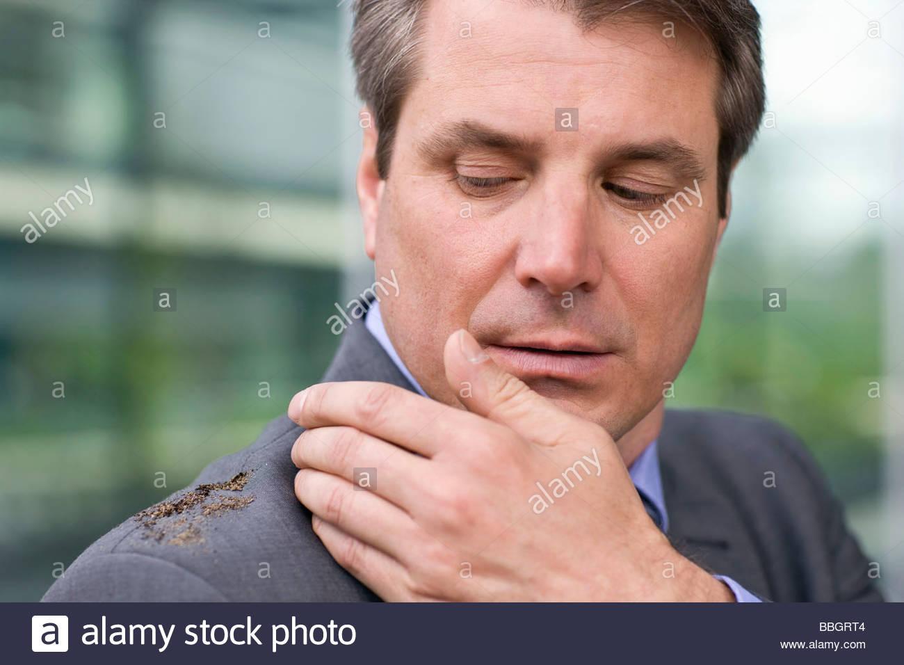 Mature businessmen brushing dirt off shoulder - Stock Image