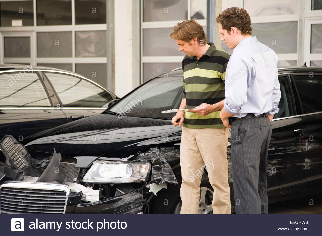 Insurance adjuster assessing damage to car - Stock Image
