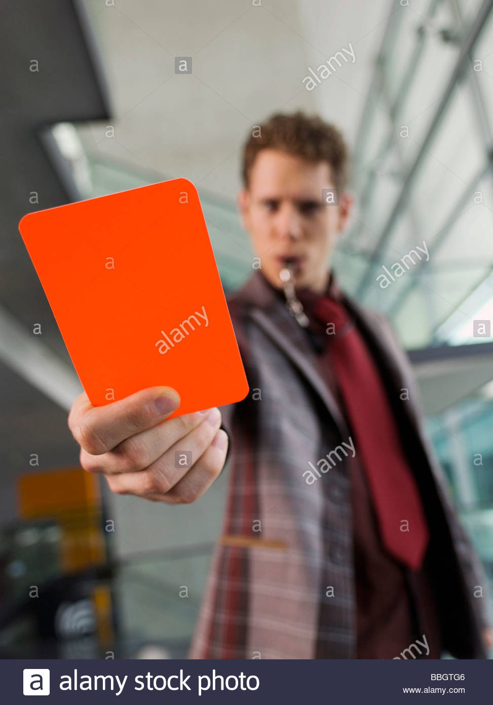 Man suit holding penalty red card - Stock Image