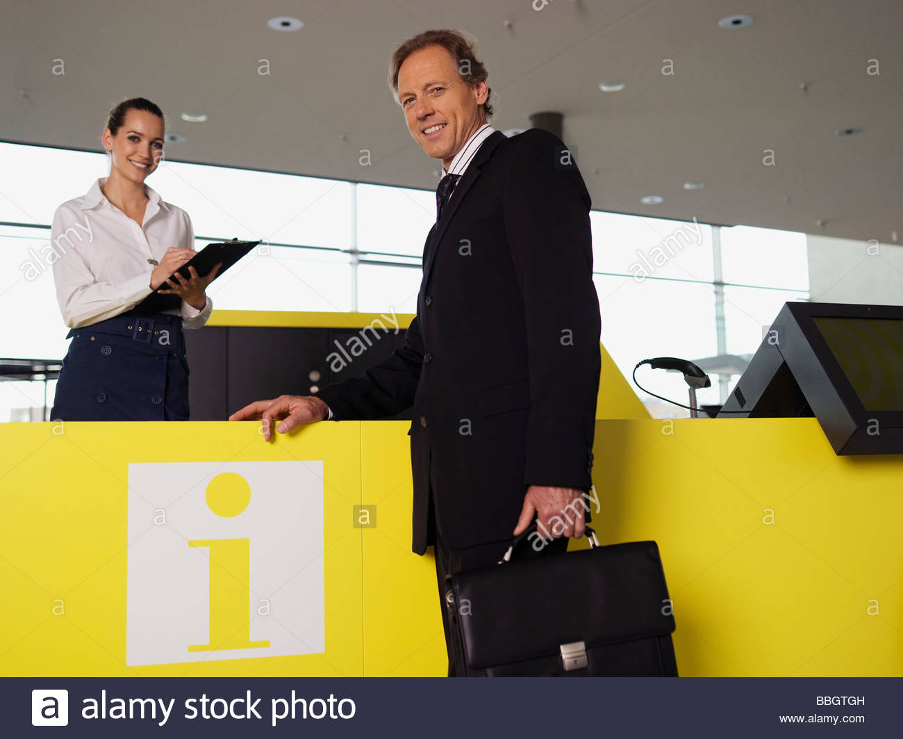 Woman at information desk helping businessman - Stock Image