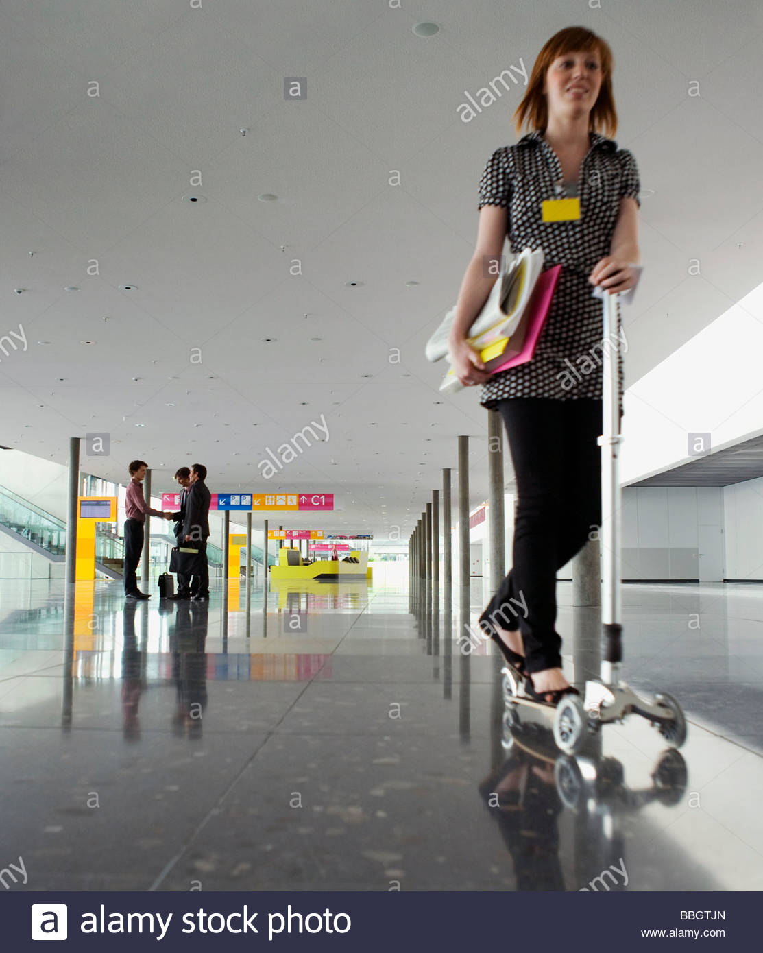 Woman riding push scooter conference center - Stock Image