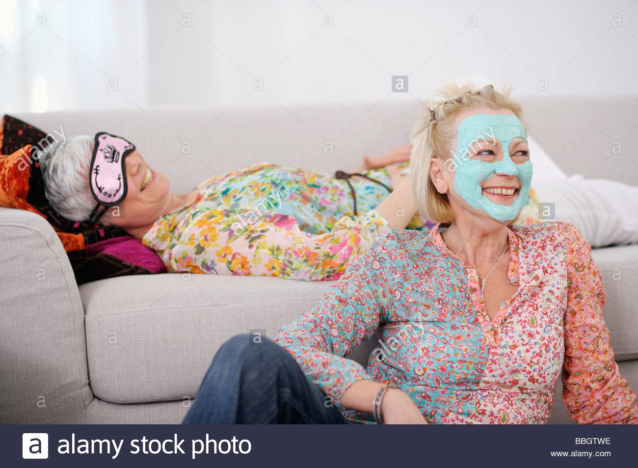 Senior women pampering themselves and relaxing living room - Stock Image