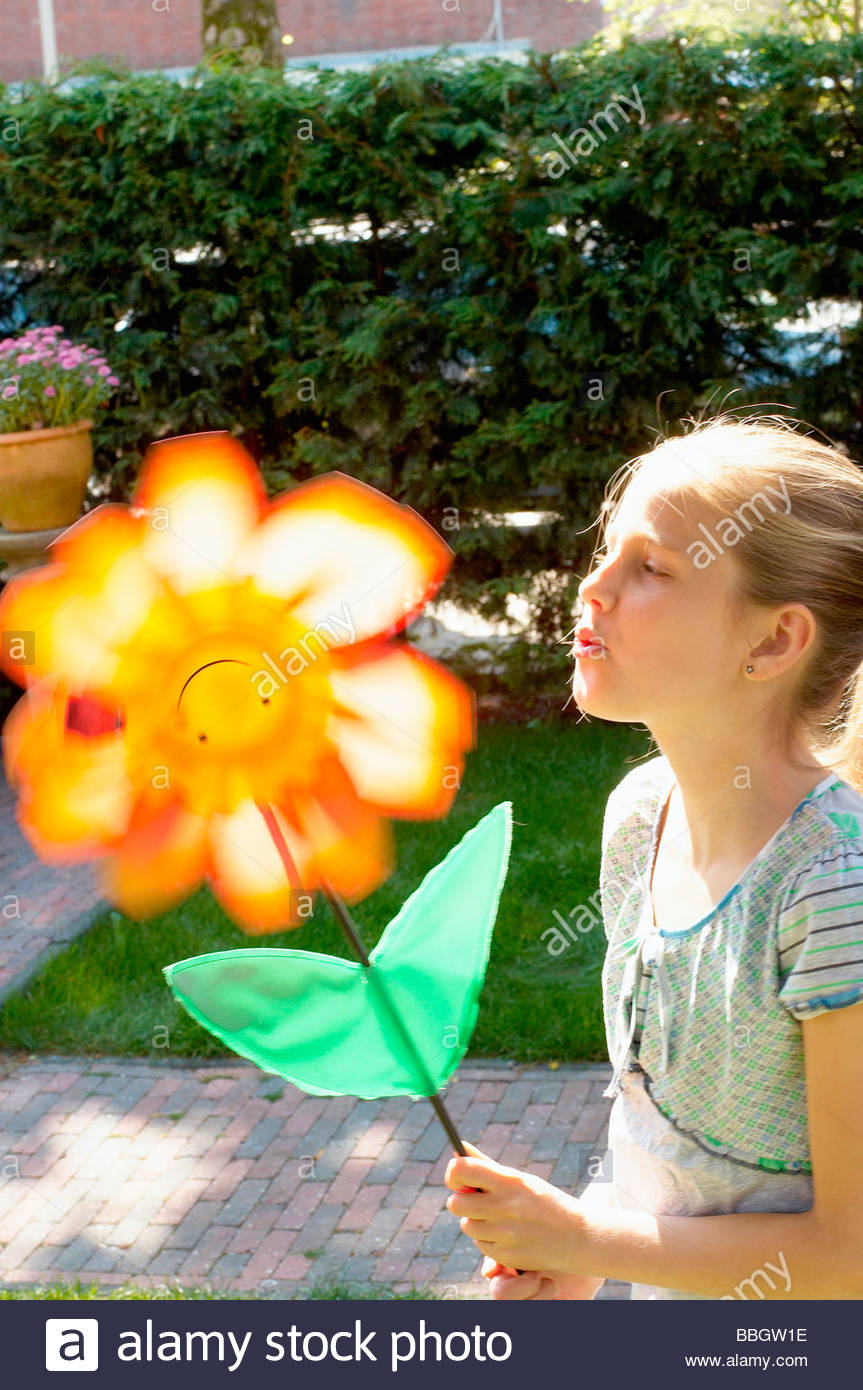 Girl blowing artificial flower, side view, Den Haag, Netherlands - Stock Image