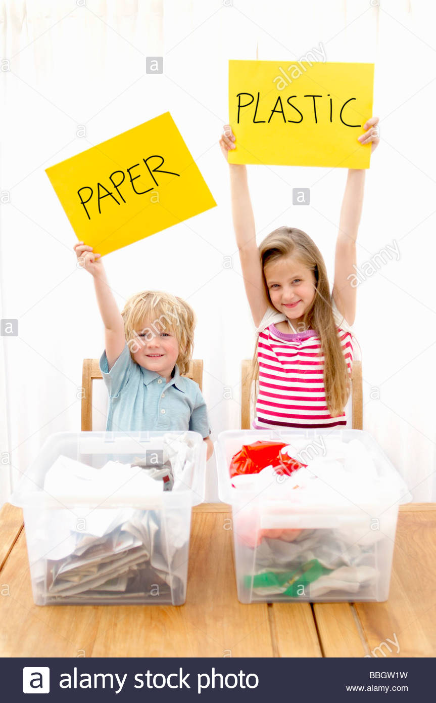 Boy and girl holding paper and plastic sign with recycling containers foreground, Den Haag, Netherlands - Stock Image