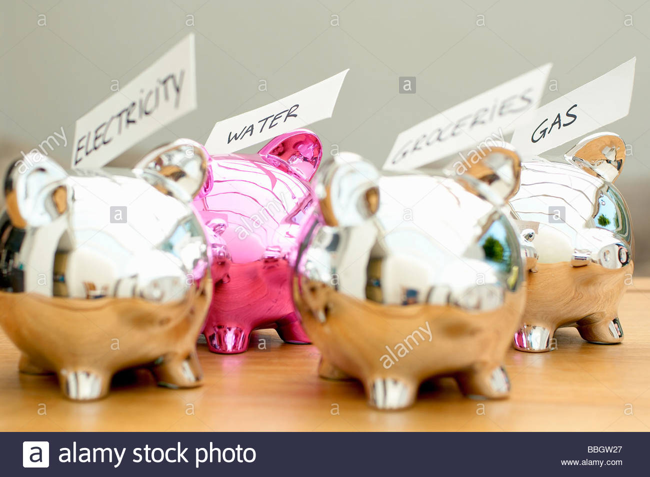 Four piggybanks with labels, focus on piggybanks with water and gas label, close-up, Den Haag, Netherlands - Stock Image