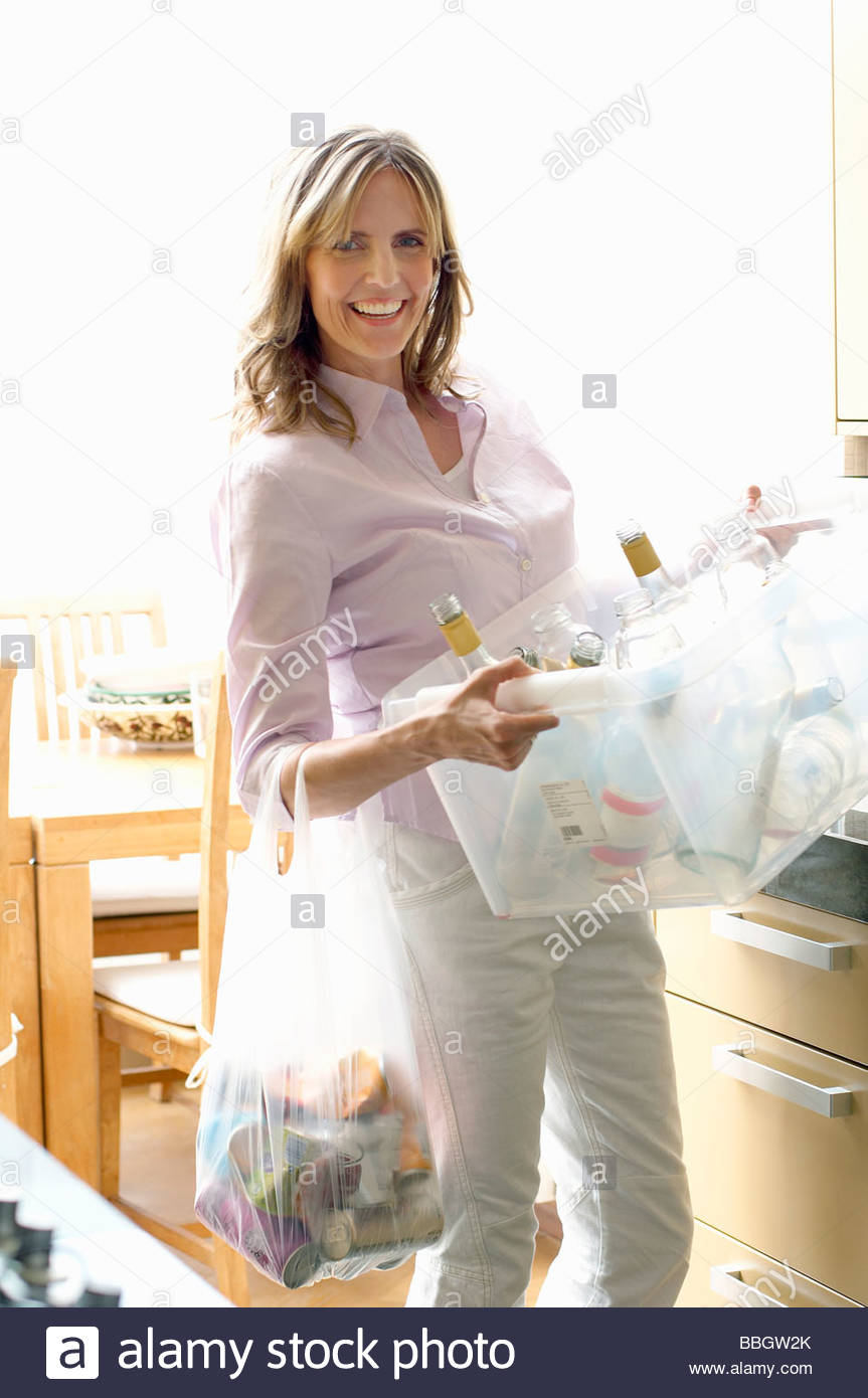 Mature woman holding recycling container glass bottles - Stock Image