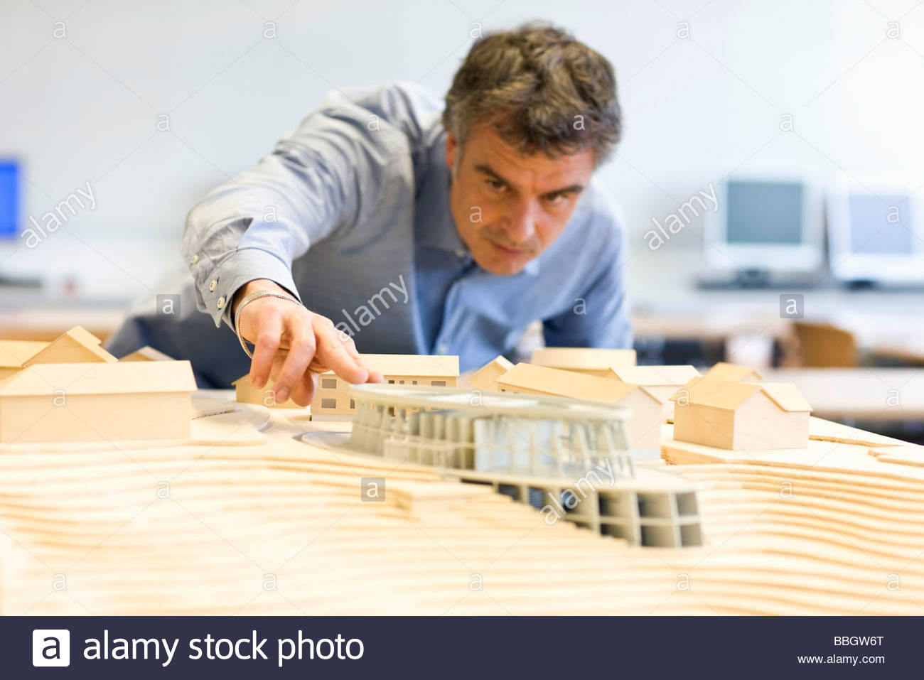 Mature man scrutinizing an architectural model - Stock Image