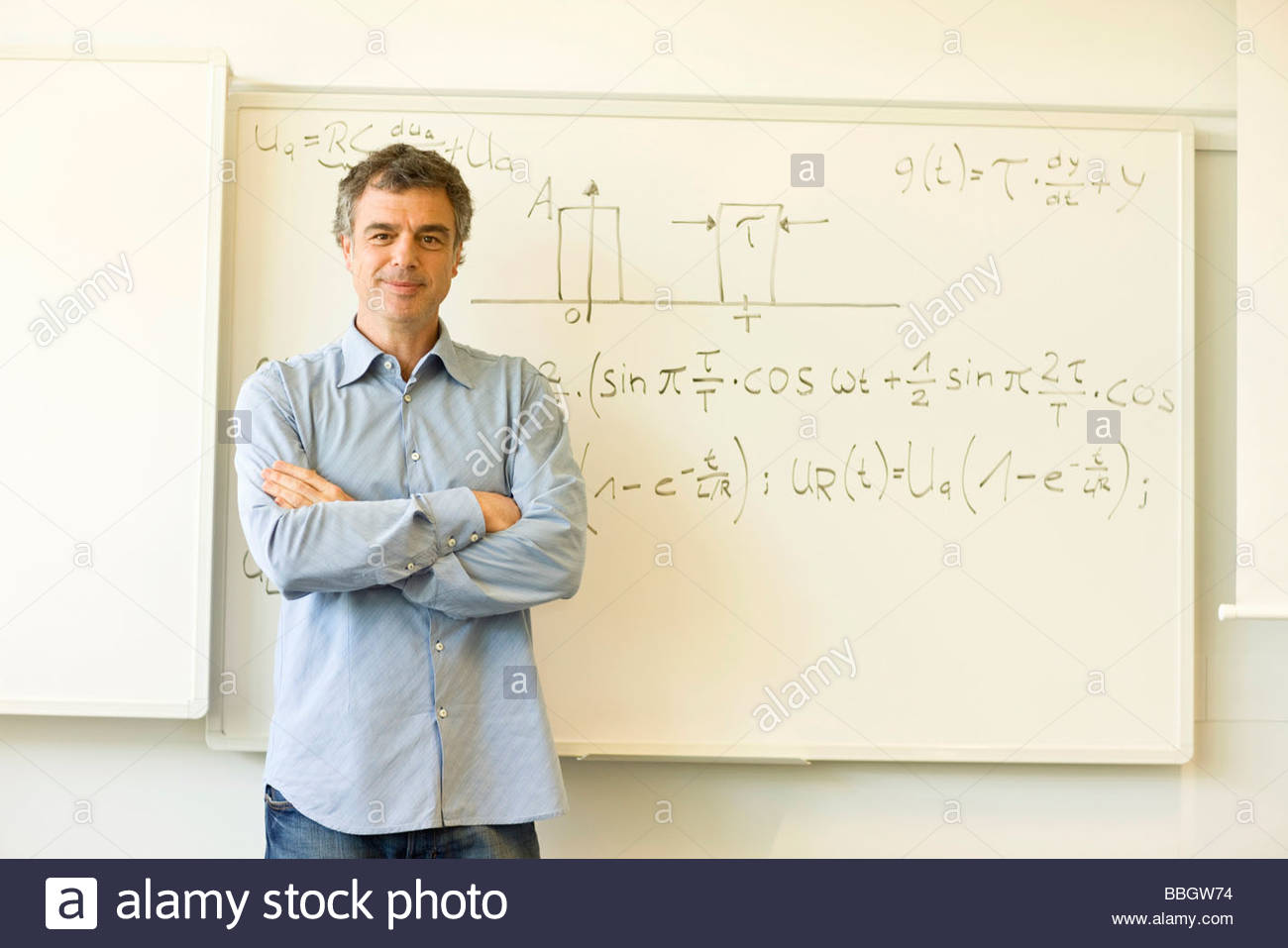 Portrait male teacher smiling before equation written on board - Stock Image