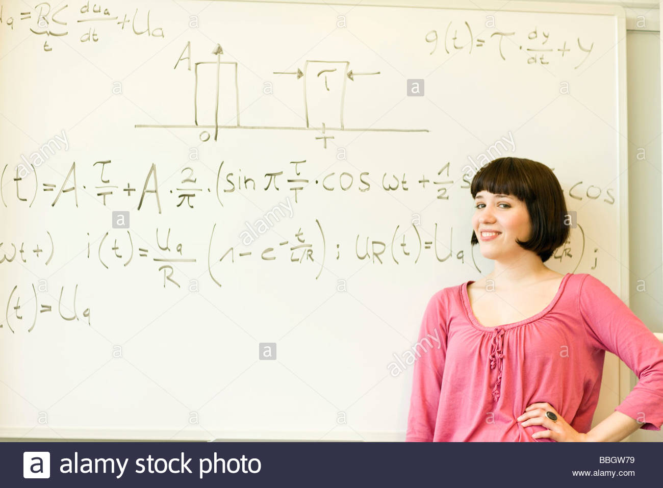 Smiling young woman posing before equation written on board Stock Photo
