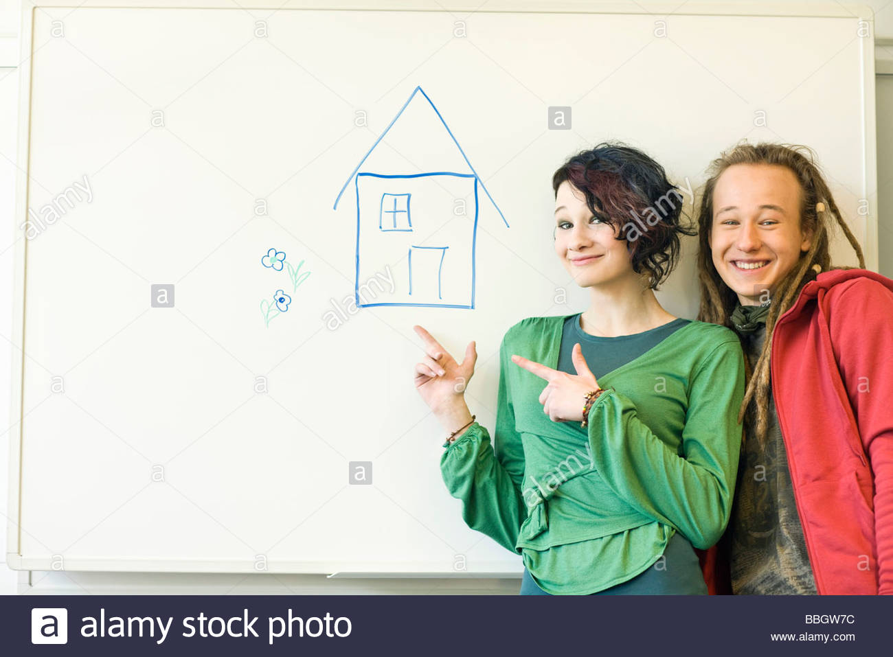 Two teenagers smiling at one another before a drawing a house - Stock Image