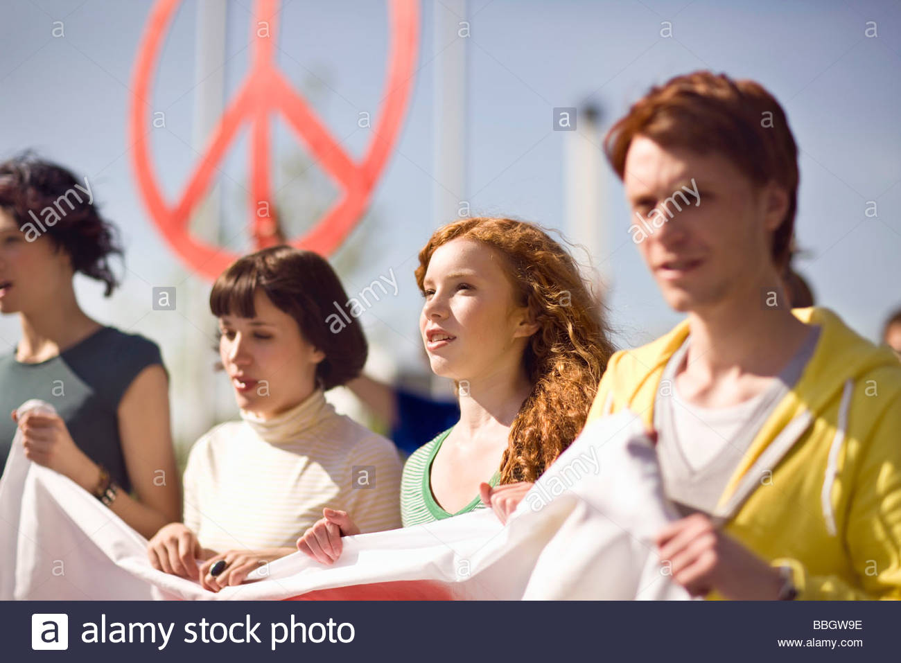Four young people holding banner at peace demonstration Munich, Bavaria, Germany - Stock Image