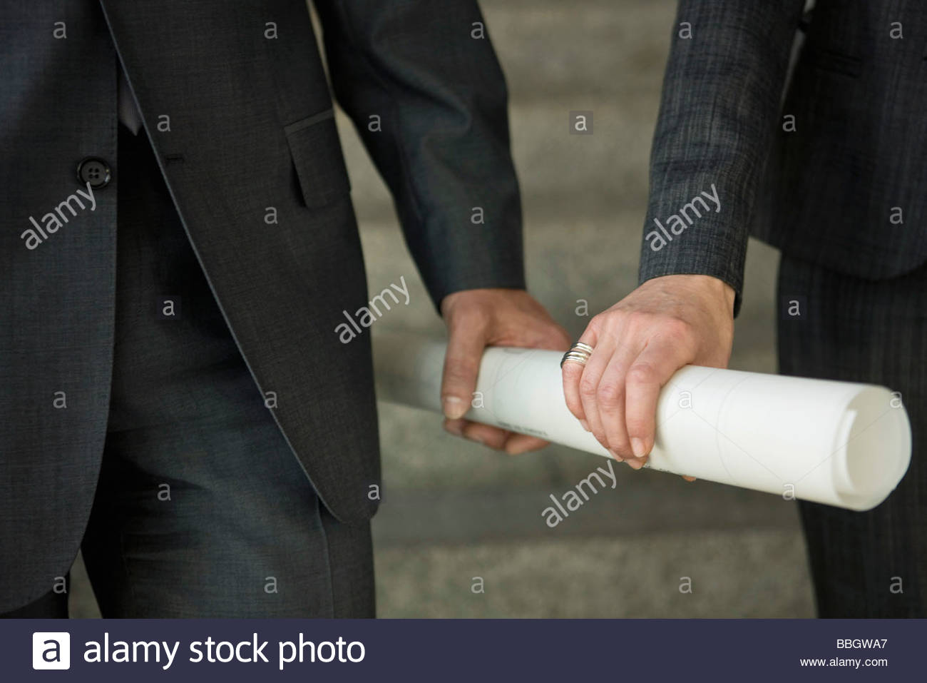 Close-up two hands holding rolled up paper - Stock Image