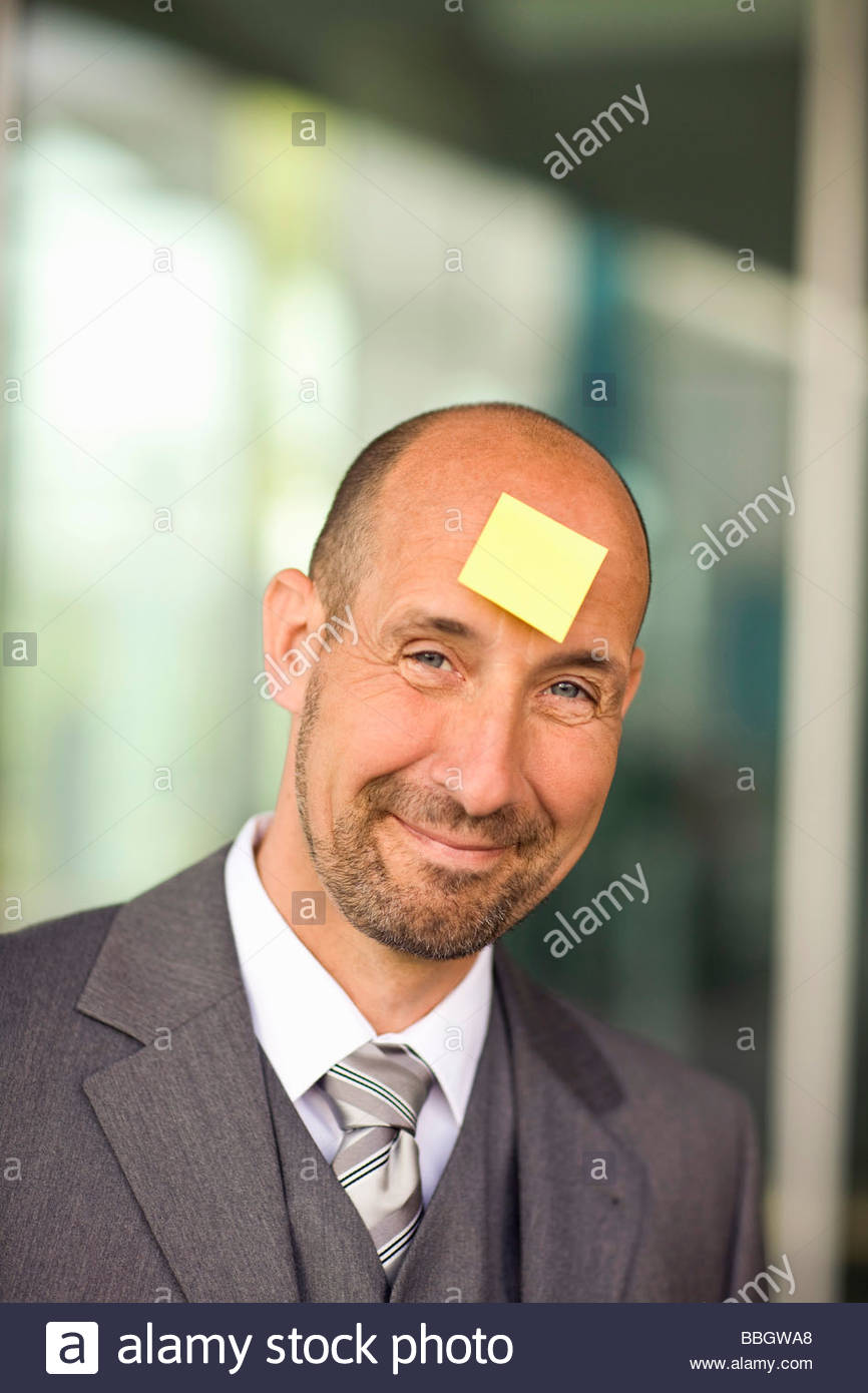 Portrait mature man with note paper stuck on forehead Stock Photo