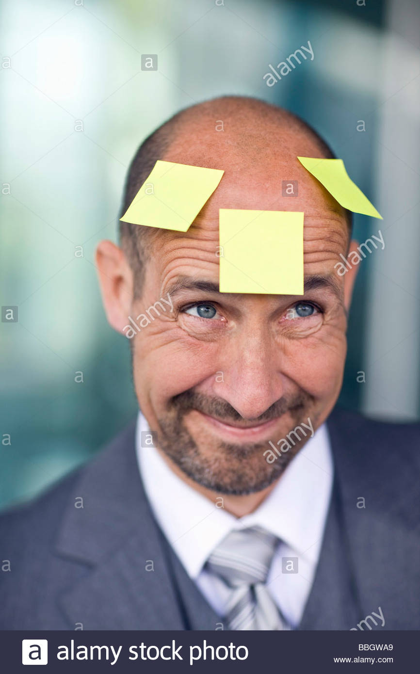 Portrait mature man with three note papers stuck on forehead - Stock Image