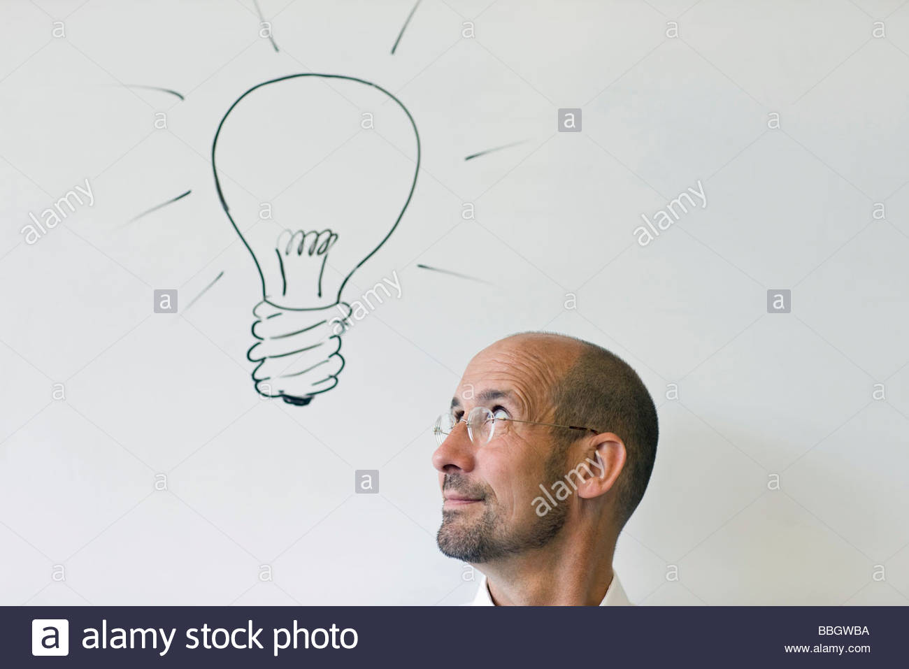 Headshot mature man looking up at line drawing light bulb - Stock Image
