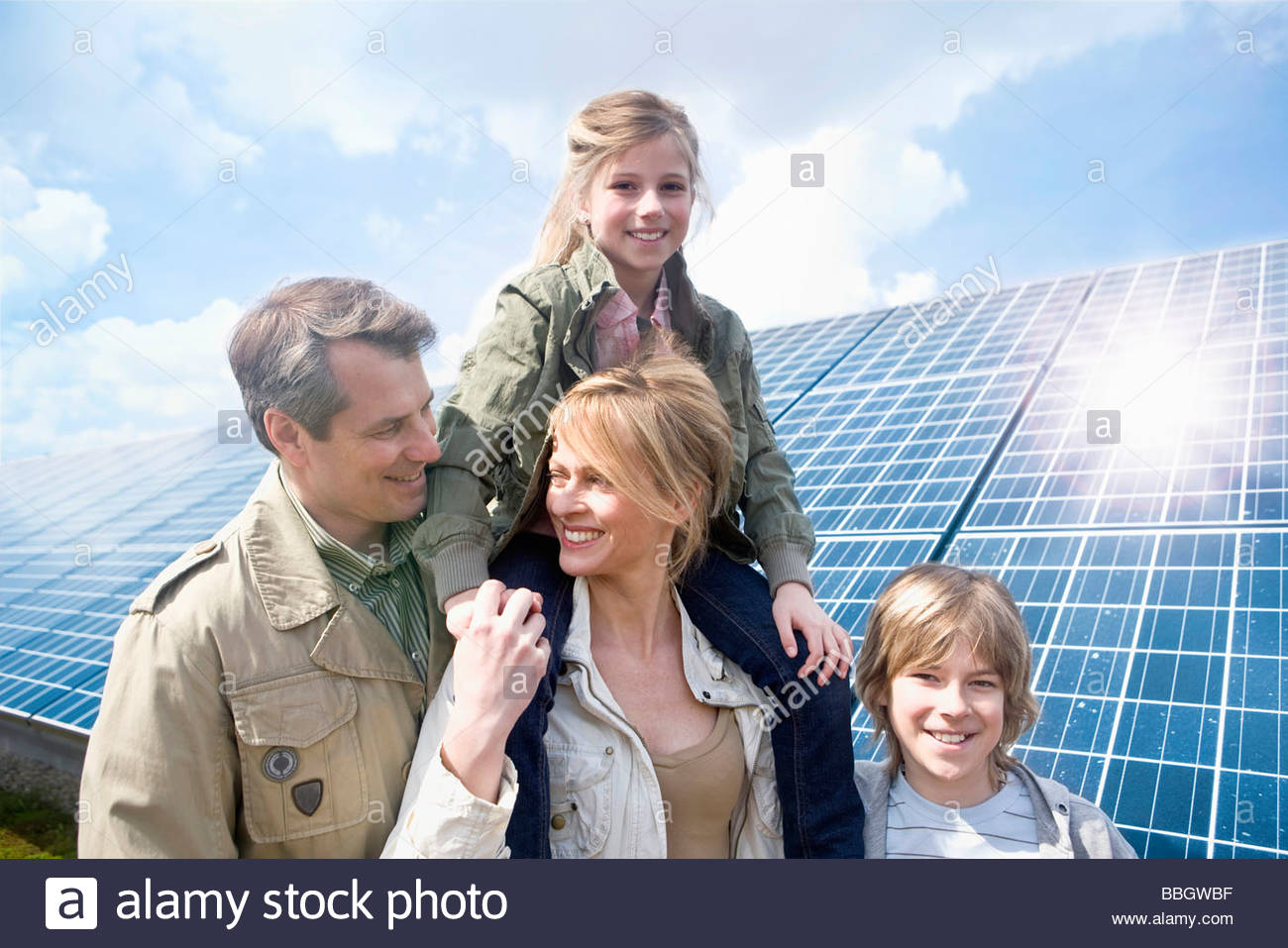 Family posing together front solar panels Munich, Bavaria, Germany - Stock Image