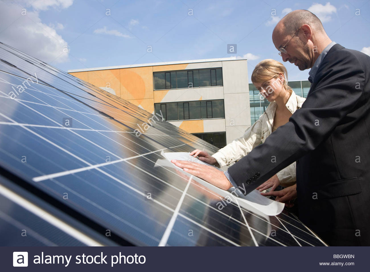 Two mature adults reading plans laid on solar panels Munich, Bavaria, Germany Stock Photo