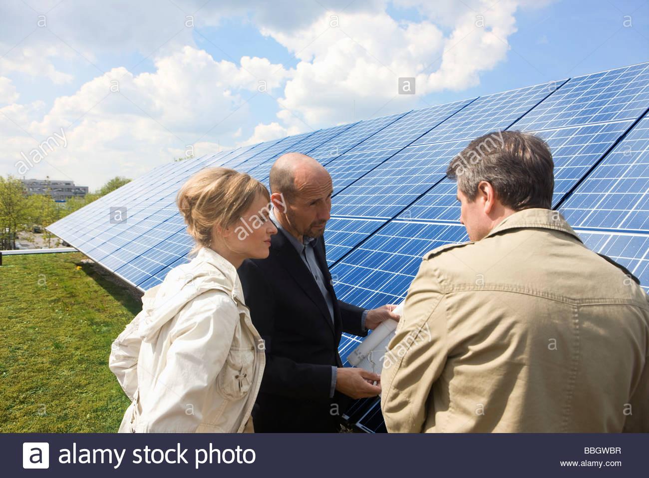 Three mature adults reading plans laid on solar panels Munich, Bavaria, Germany - Stock Image