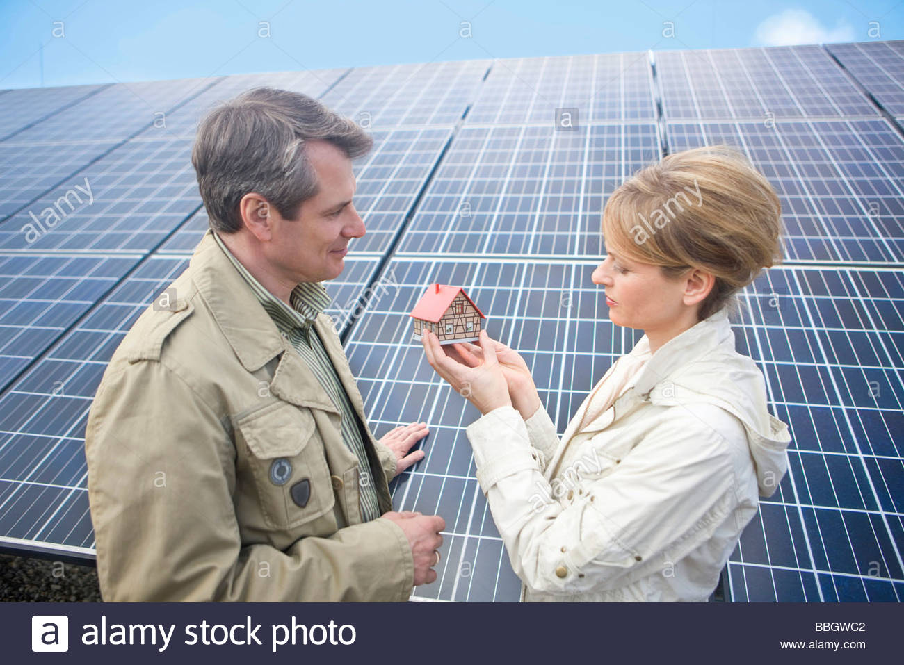 Mature couple standing front solar panels holding miniature house Munich, Bavaria, Germany - Stock Image