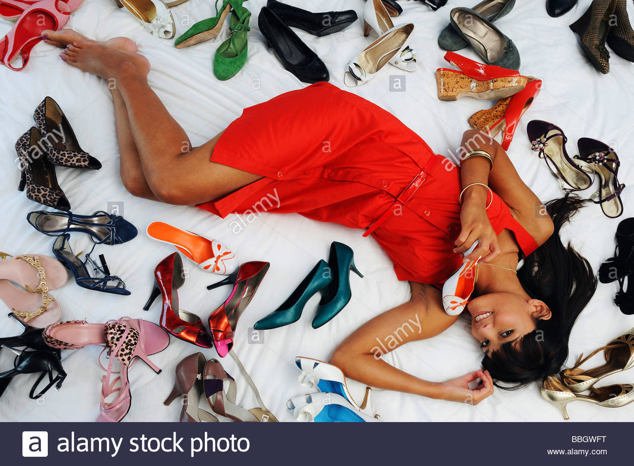 Portrait a young woman surrounded by shoes on a bed - Stock Image
