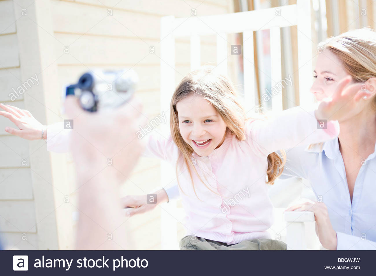 Mother and daughter being video taped - Stock Image