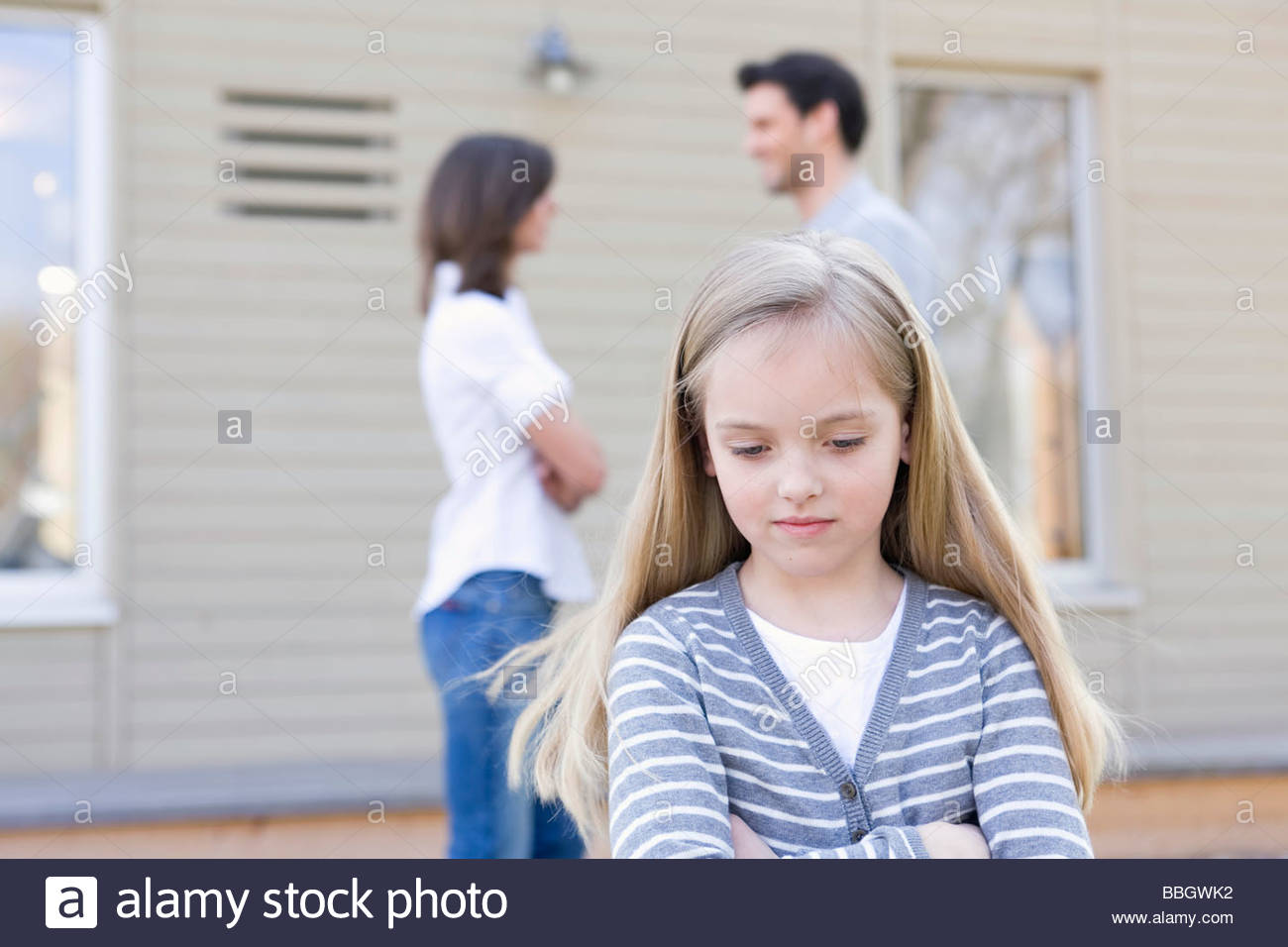 Portrait young girl standing separately from her parents - Stock Image