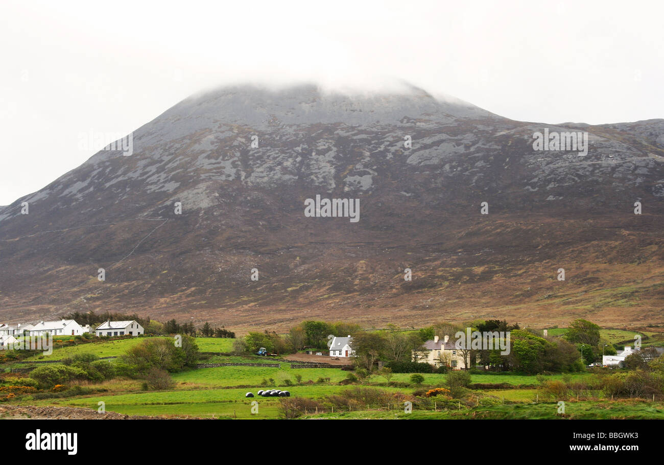 Croagh Patrick Mountain, top covered in cloud. Cottages and farmland. County Mayo, West coast of Ireland. - Stock Image