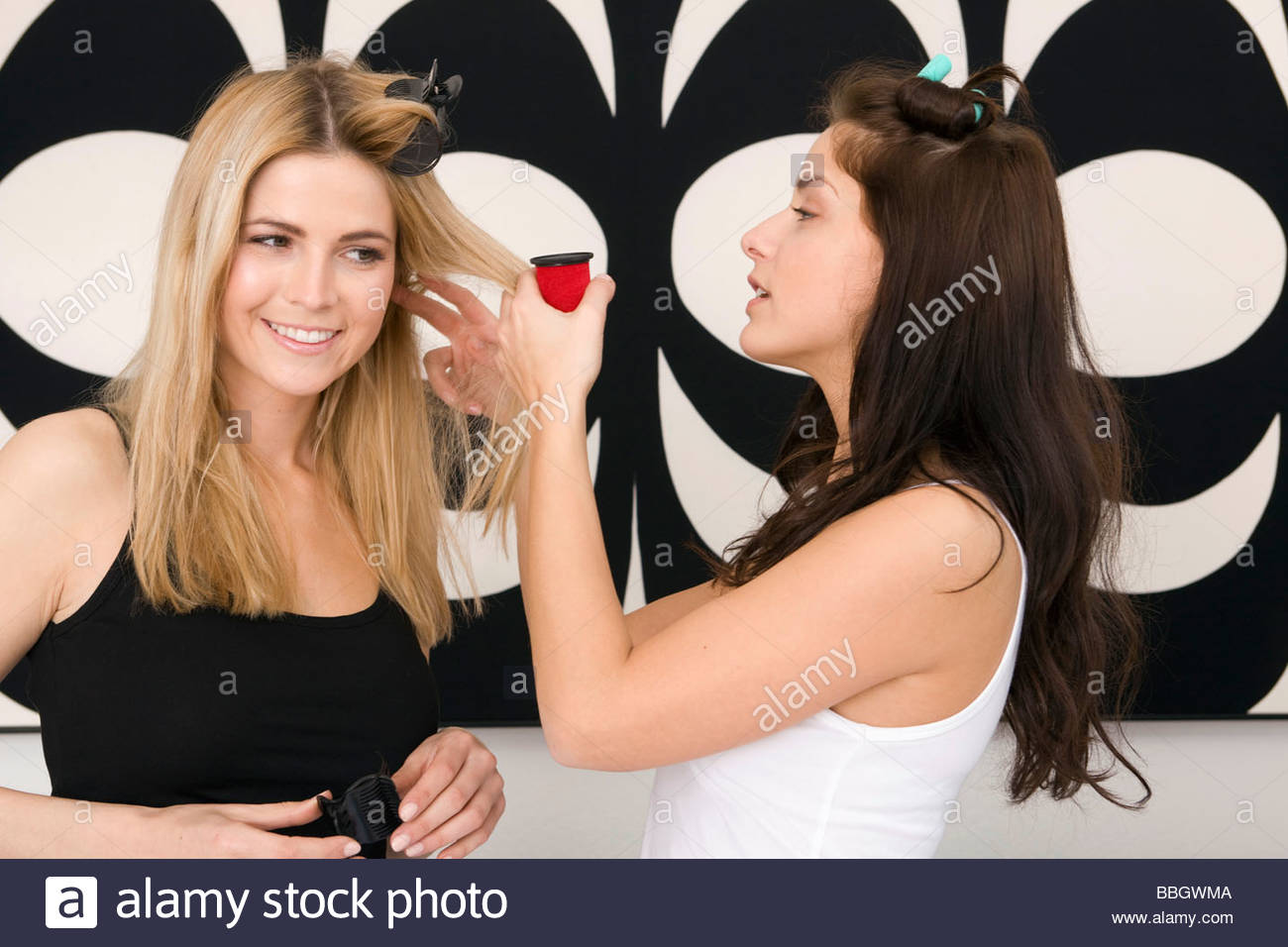 Two young women styling each others hair - Stock Image