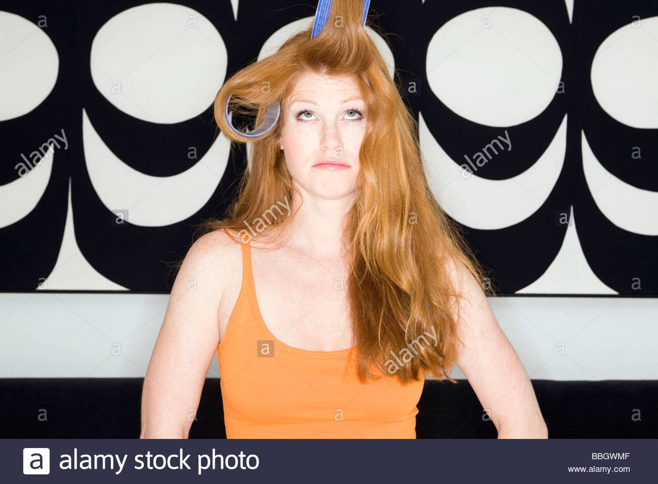 Young woman with her hair rollers - Stock Image