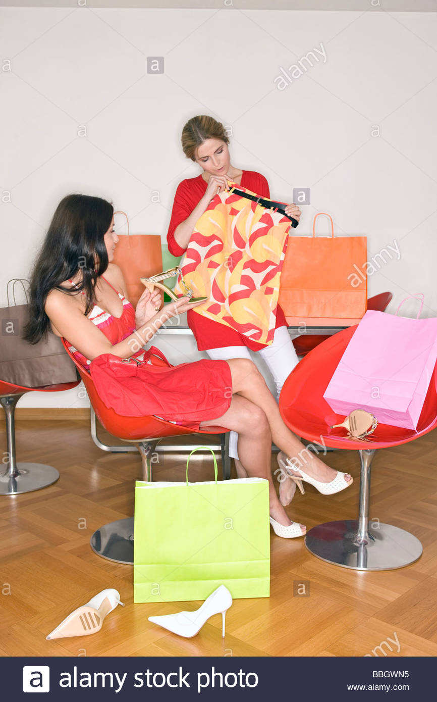 Two women looking at their shopping purchases - Stock Image