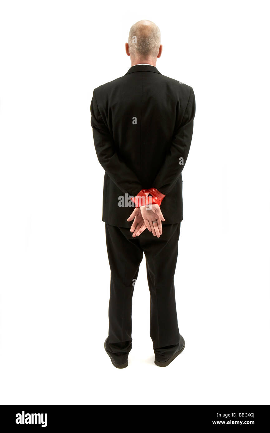 BUSINESSMAN WITH HANDS TIED WITH RED TAPE - Stock Image