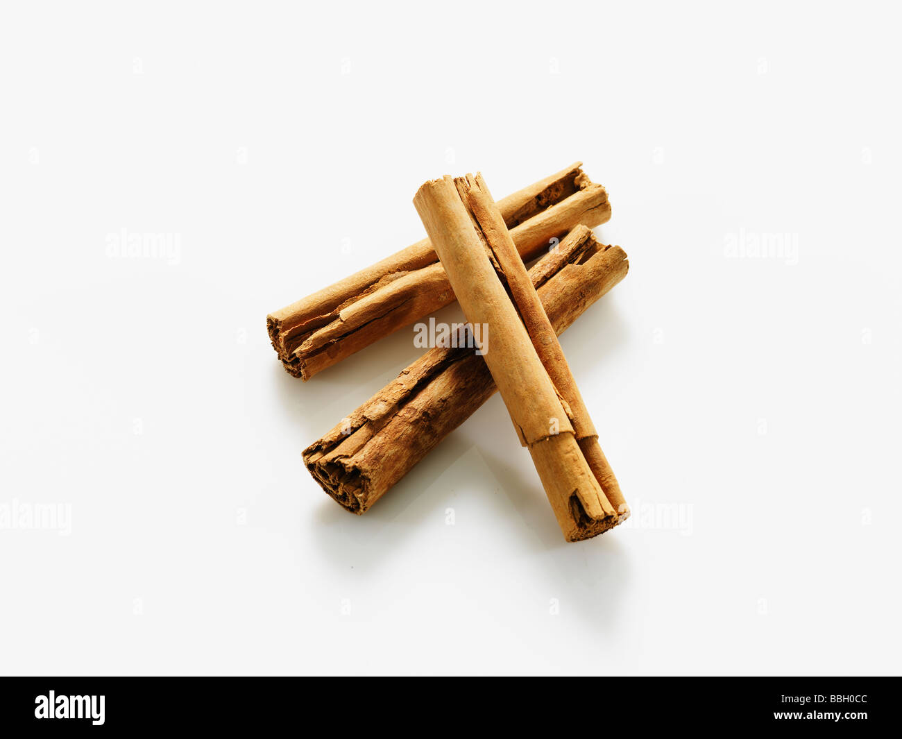 Cinnamon sticks overlaying on white studio background - Stock Image
