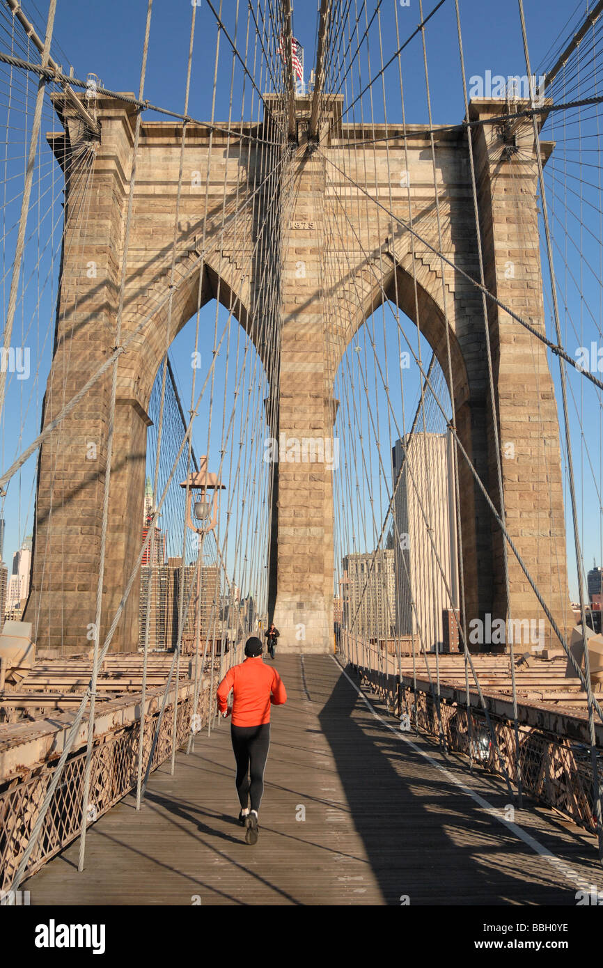 Man running into Manhattan on the Brooklyn Bridge New York City New York USA Stock Photo