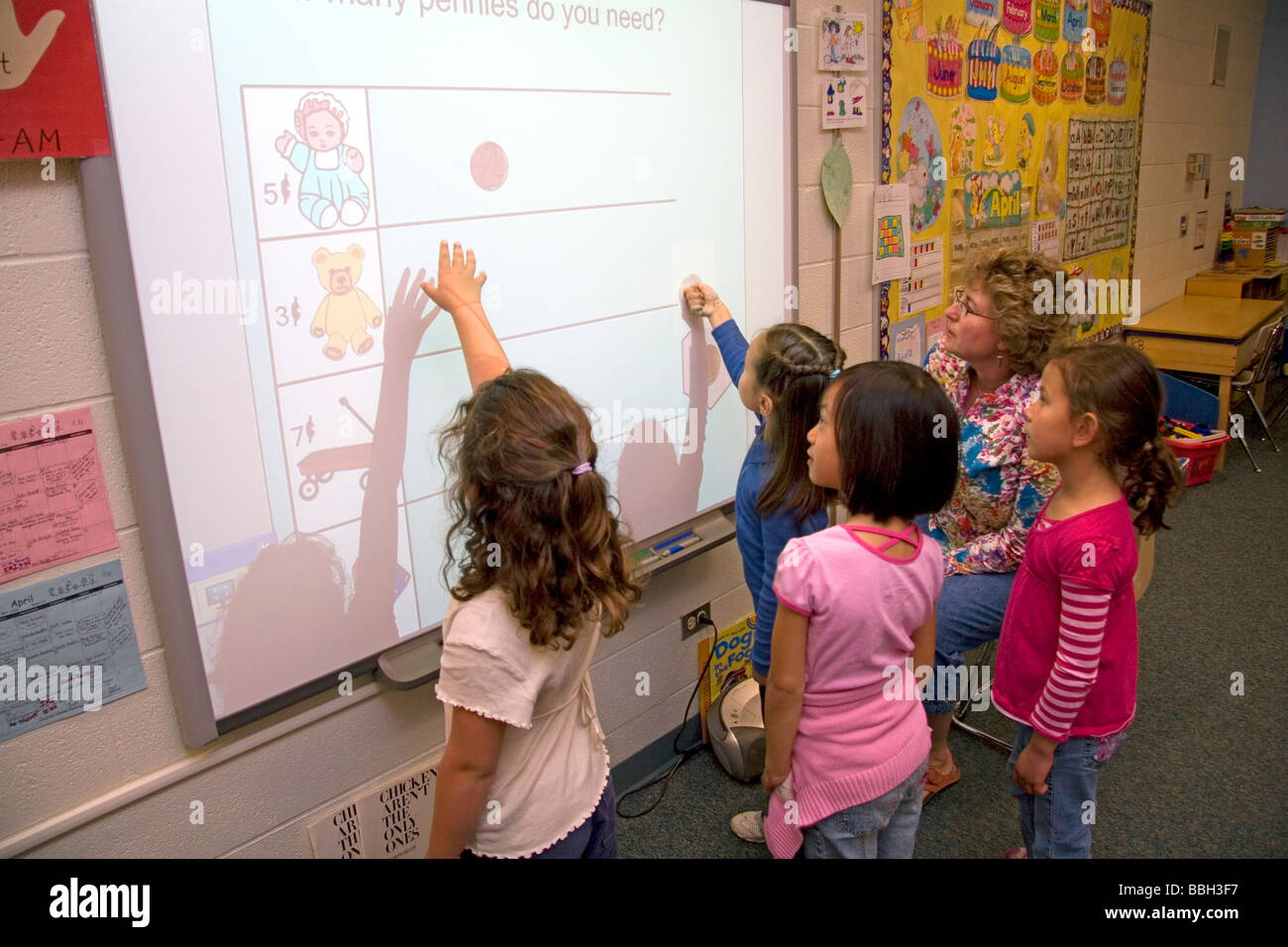 Kindergarten students use an interactive whiteboard in the ...