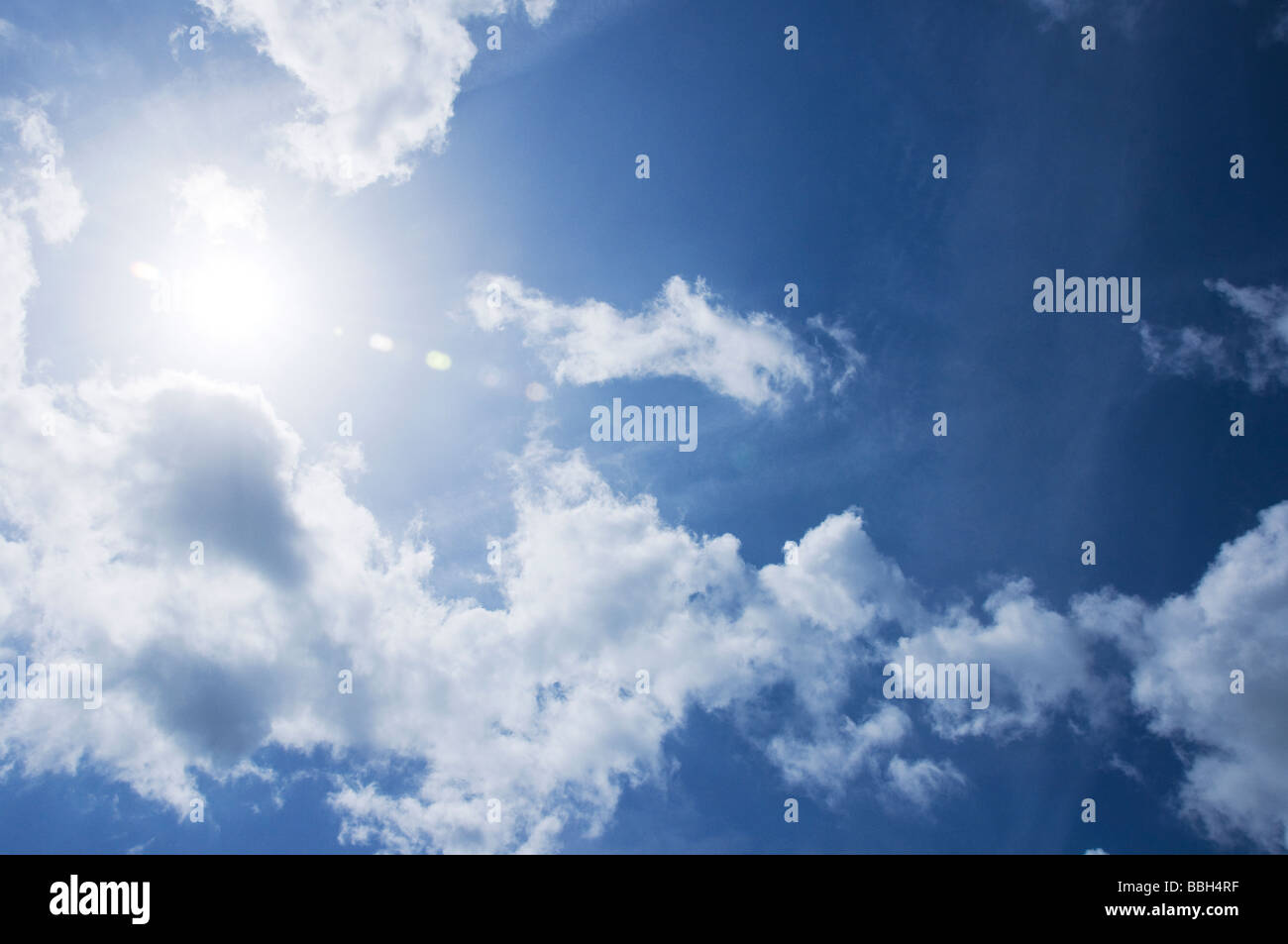 Looking at sun during the day against a blue and cloudy sky - Stock Image