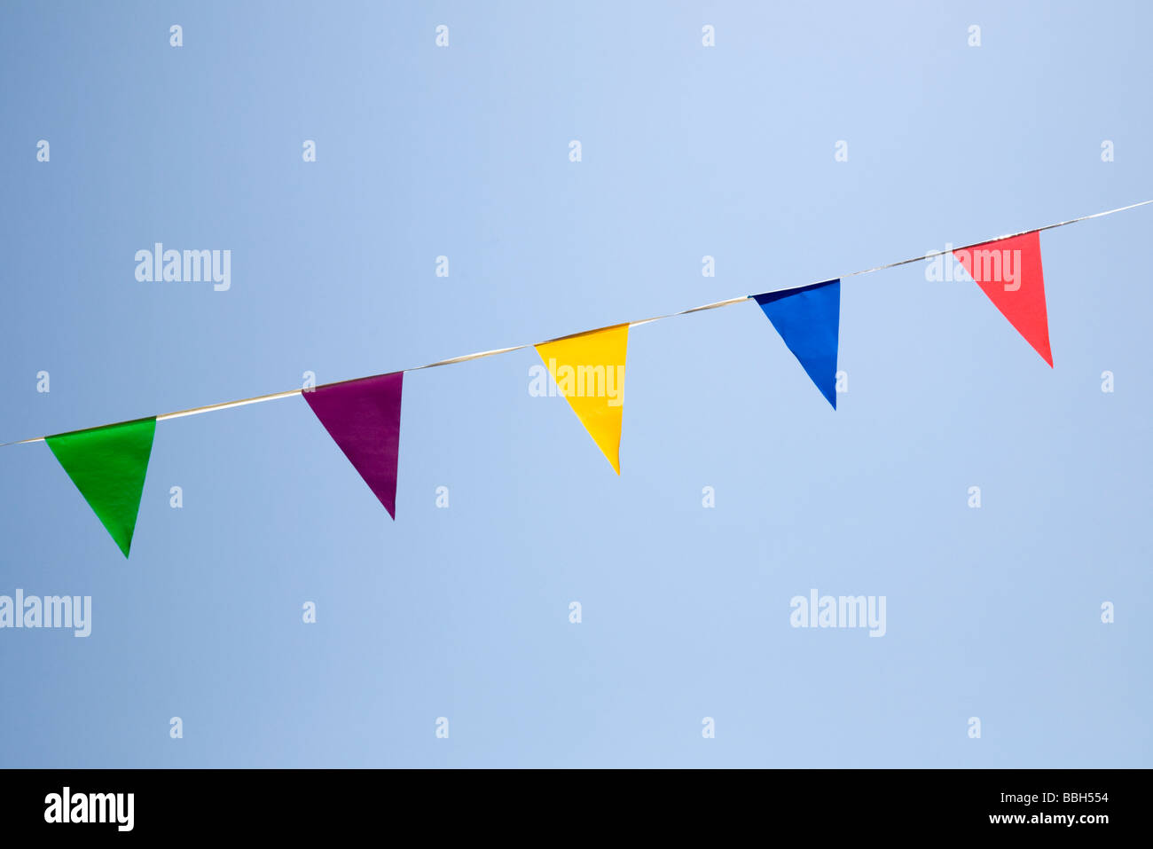 Bunting - triangular flags of different colours against a blue sky - Stock Image