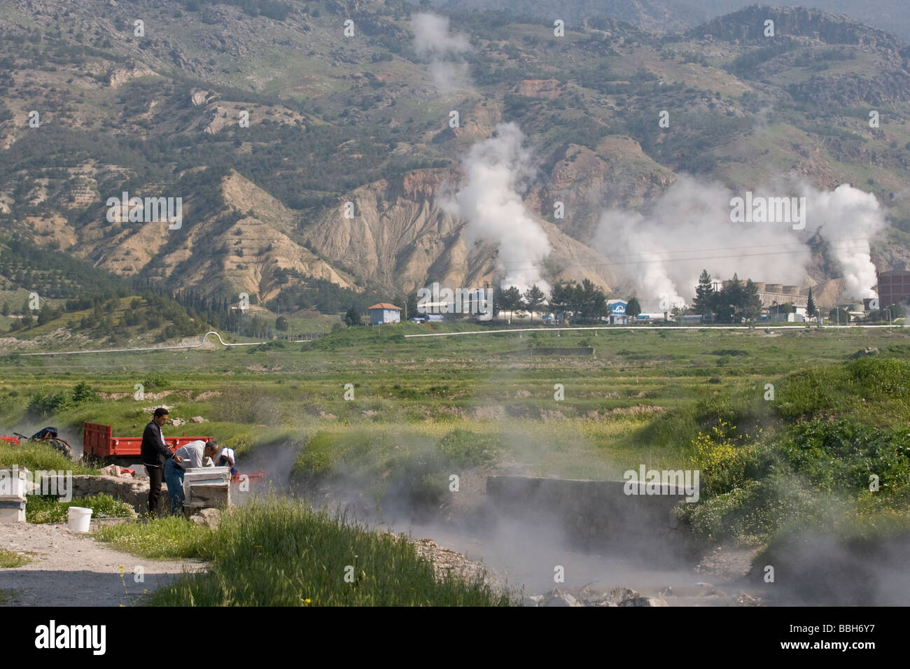 Bee keepers in Turkey cleaning their wooden hives in a stream heated by thernal steam vents - Stock Image
