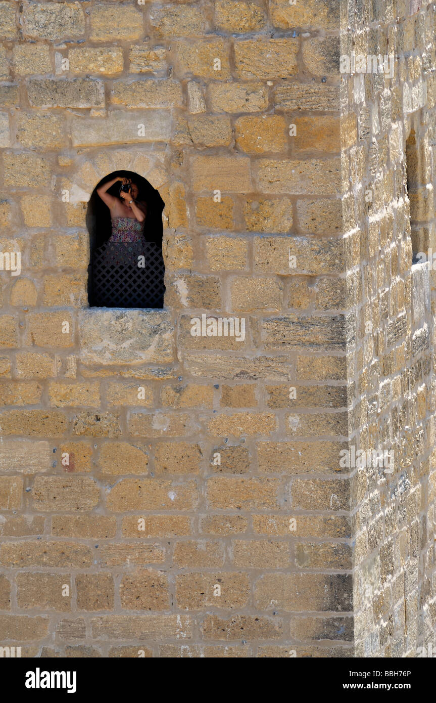 Woman with camera looking out of small window of stone tower - Stock Image