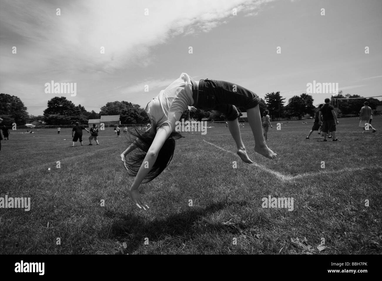 A teenage girl does a backflip on a field during recess at her High School in Connecticut USA - Stock Image
