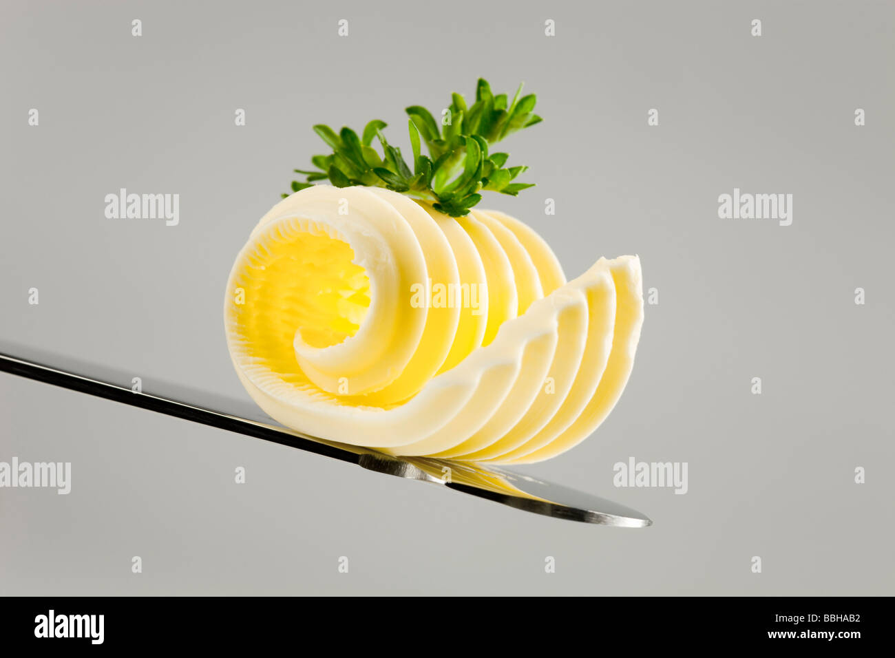 Butter curl on a knife - Stock Image