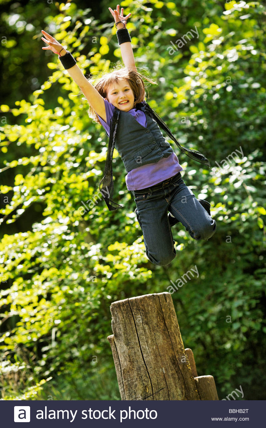 10year old girl jumps from a stump - Stock Image