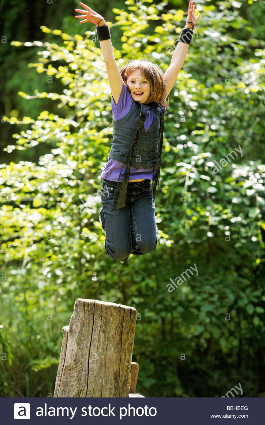 10year old girl jumps from a stump Stock Photo