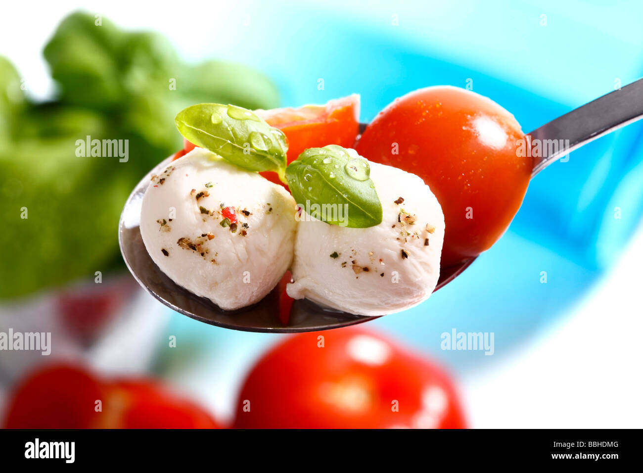 Tomatoes, mozzarella and basil on a spoon Stock Photo