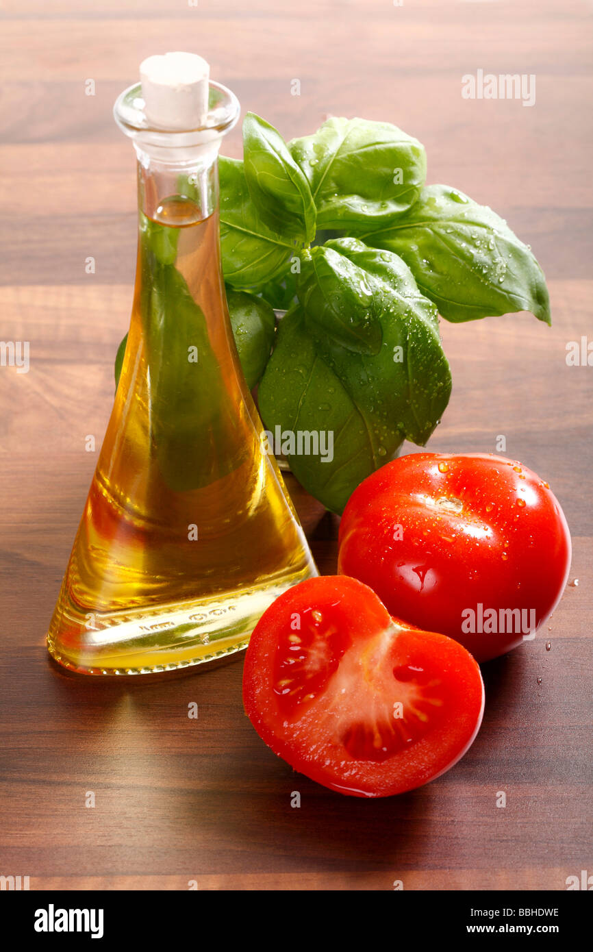 Tomatoes, olive oil and fresh basil on a wooden table Stock Photo
