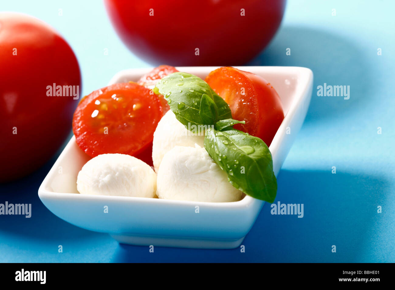 Tomatoes and mozzarella with basil on a dish Stock Photo